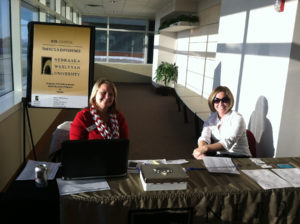 Kristy-and-Bridget-welcome-attendees-to-NE-Wesleyan-U-IMG_8715-2
